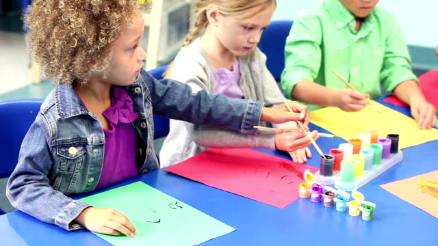 Group of multi-ethnic children painting in art class video