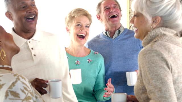 Group of multi-ethnic seniors socializing over coffee video