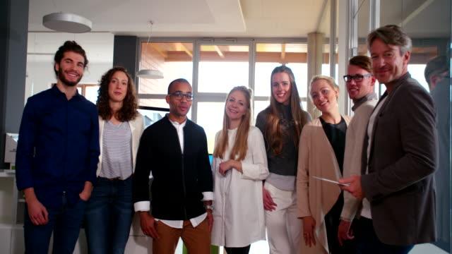 vídeos de stock, filmes e b-roll de grupo de multi-étnico inicialização empresário posando para foto de escritório de negócios. - gênero humano