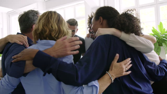 Group of multiracial business team in a huddle Group of multiracial business people standing in huddle at office. Diverse business team standing together in a circle. hug stock videos & royalty-free footage