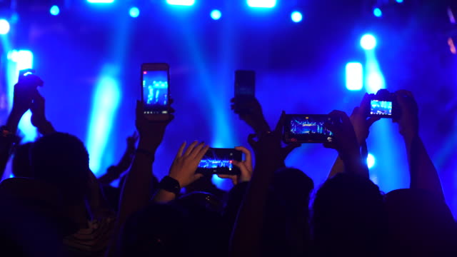 Group of music fans recording concert with mobile phones