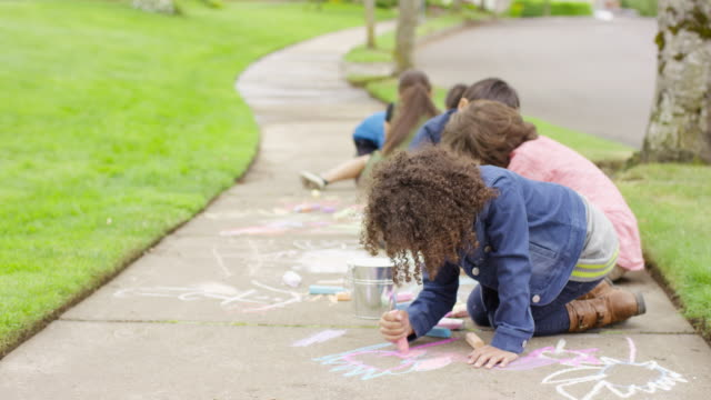 Group of neighborhood children playing together outside with sidewalk chalk video