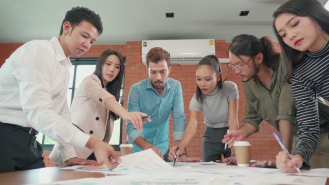 stockvideo's en b-roll-footage met groep kantoormedewerkers die brainstormen en samenwerken in kantoor - aziatische etniciteit