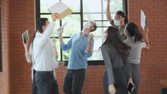stockvideo's en b-roll-footage met groep bureauarbeiders die en samen het dragen van gezichtsmasker in bureau dansen en vieren om covid-19 te beschermen - aziatische etniciteit