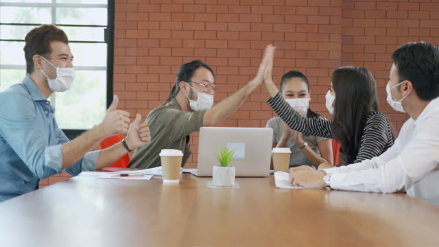 Group of Office workers meeting and wearing face mask in office to protect COVID-19