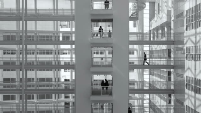 group of office workers walking on elevated walkway - black and white architecture stock videos & royalty-free footage