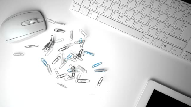 Group of paperclips spilling onto office desk video
