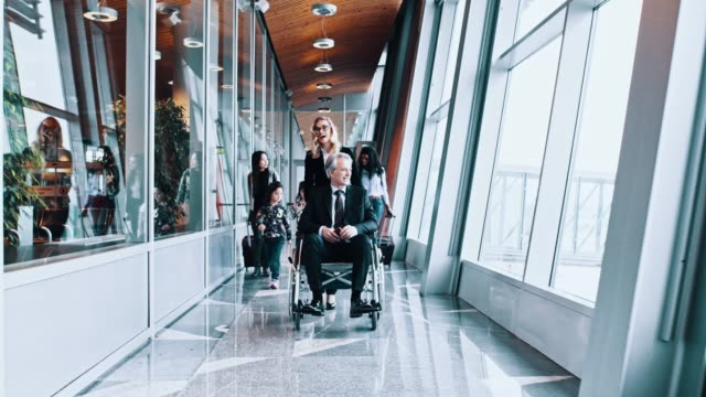 A group of passengers including a senior man on wheelchair passing the corridor in the airport A group of passengers including a senior man on wheelchair passing the corridor in the airport. wheelchair stock videos & royalty-free footage