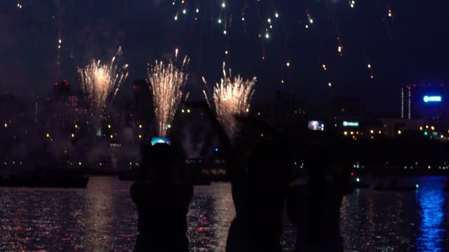 A group of people are happy during a beautiful firework display. slow motion A group of people are happy during the beautiful fireworks near the river. slow motion. family 4th of july stock videos & royalty-free footage