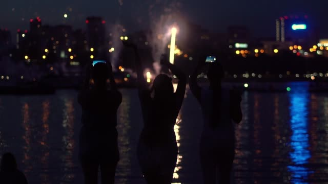 A group of people are happy during the fireworks. slow motion. HD A group of people are happy during the fireworks near the river. slow motion. HD family 4th of july stock videos & royalty-free footage