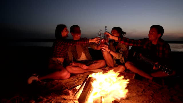 Group of people are spending time near the bonfire on the beach at night. Drinking alcohol, cheers. Young man is holding a guitar. Front view - video