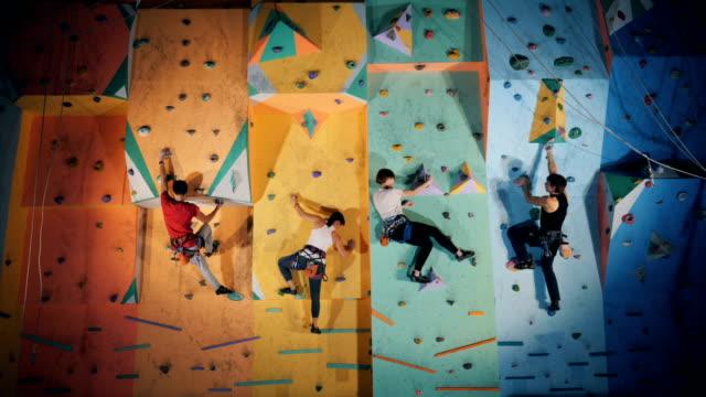 gruppe von menschen nehmen an einer clambering-übung in einem fitnessstudio teil - bouldering stock-videos und b-roll-filmmaterial