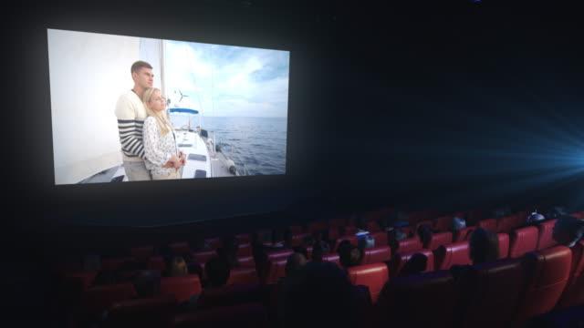 vidéos et rushes de groupe de personnes regardent un film projection dans un cinéma de cinéma. - cinéma