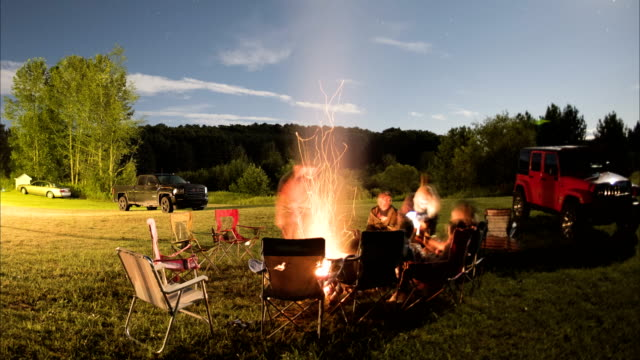 group of people around a campfire on a beautiful summer night - camping stock videos & royalty-free footage