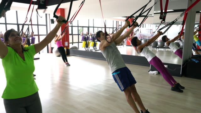 Group of people at a gym class working out with suspension straps
