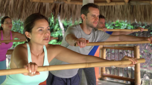 Group of people at a yoga class exercising with a bamboo stick video