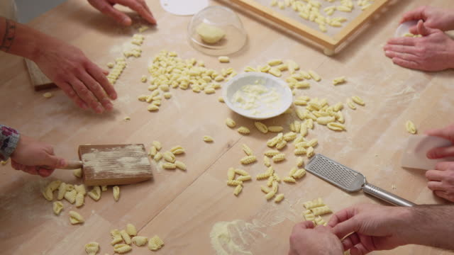 Group of people at cooking workshop making pasta