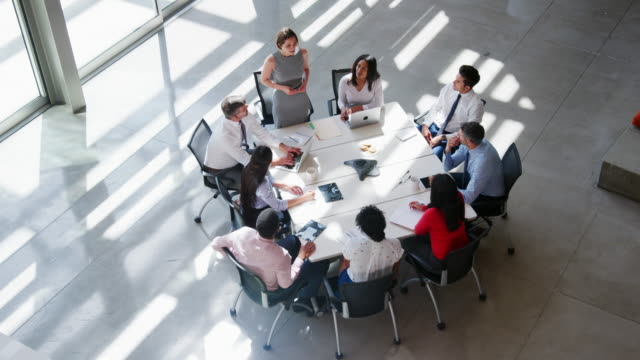 Group of people at meeting in a modern office, elevated view Group of people at meeting in a modern office, elevated view board room stock videos & royalty-free footage