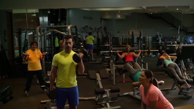 vídeos de stock e filmes b-roll de group of people at the gym working out on different machines very focused - aparelho de musculação