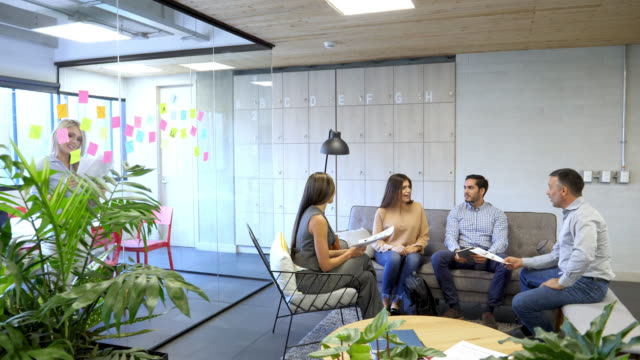 Group of people at the office discussing something while sitting on the couch and woman working behind with adhesive notes and a document all looking very happy Group of people at the office discussing something while sitting on the couch and woman working behind with adhesive notes and a document all looking very happy and smiling coworking stock videos & royalty-free footage