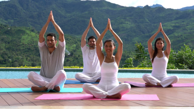 Group of people at yoga class outdoors sitting on yoga mats looking happy while doing exercises video