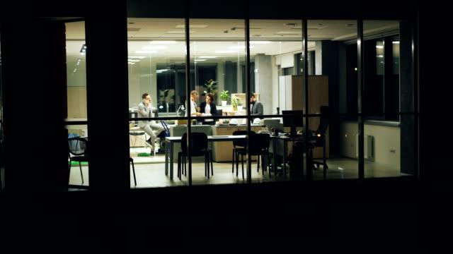 gruppe von menschen-business-team arbeitet im büro spät in der nacht telefonieren mit handy, arbeit zu diskutieren und dokumente zu betrachten. blick von außen vom panoramafenster. - panorama stock-videos und b-roll-filmmaterial