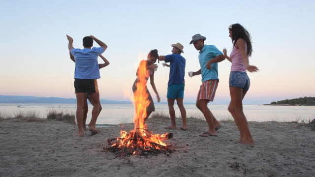 Group of people dancing by bonfire at the beach. video