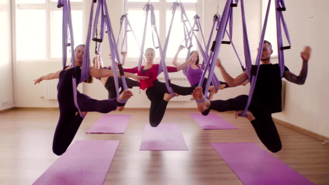 group of people doing aerial yoga in gym - бунтарство стоковые видео и кадры b-roll