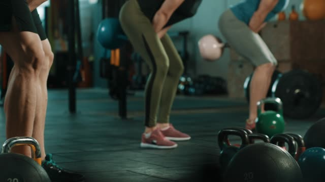 group of people doing exercise with kettlebell in gym - giria filmów i materiałów b-roll
