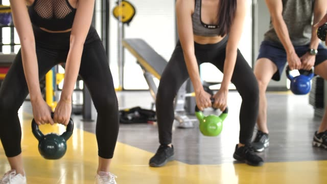 Group of People doing exercise with Kettlebell Working through the squat