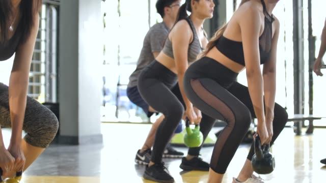 gruppe von menschen, die mit kettlebell trainieren und durch die hosquat arbeiten - fitnesskurs stock-videos und b-roll-filmmaterial