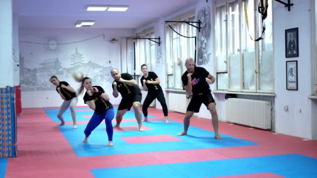 vídeos de stock, filmes e b-roll de grupo de pessoas fazendo a coreografia de treino - autodefesa