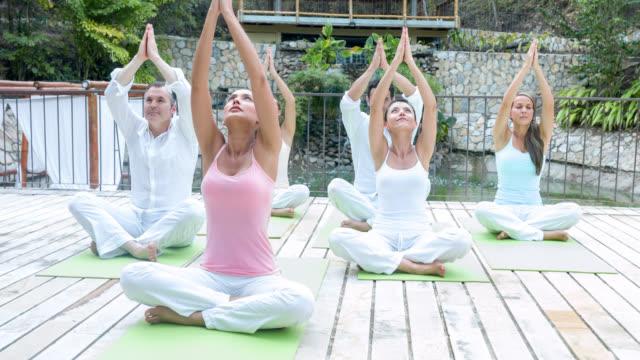 gruppo di persone facendo yoga - arto umano video stock e b–roll