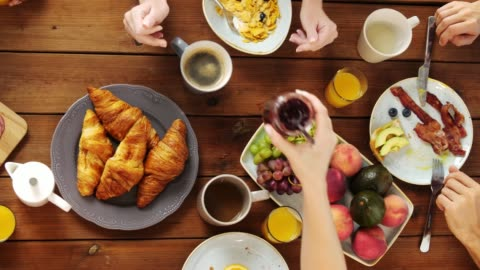 group of people eating at table with food eating and leisure concept - group of people having breakfast at table with food breakfast stock videos & royalty-free footage