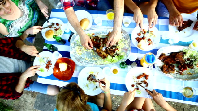 Group of people eating, top view. Group of mid 20's caucasian people having lunch outdoors.There are three guys and four girls.They are sitting at wooden table  with two big serving plated with meat and vegetables. Top view. garnish stock videos & royalty-free footage