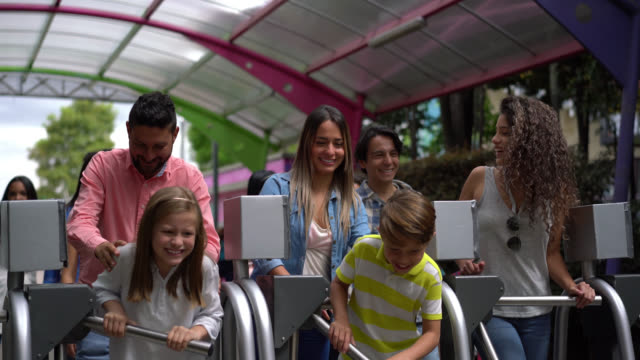 Group of people entering an amusement park passing the turnstiles all looking very happy