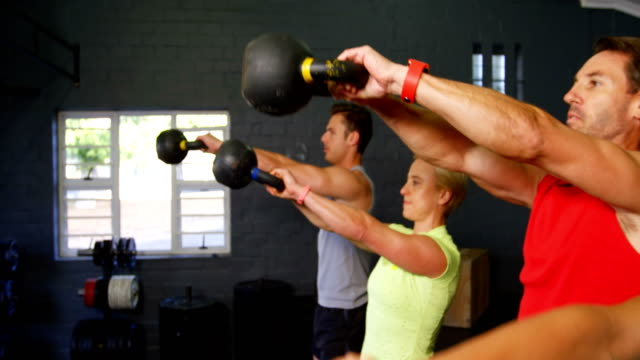 Group of people exercise with kettlebell Group of people exercise with kettlebell in gym mid adult stock videos & royalty-free footage