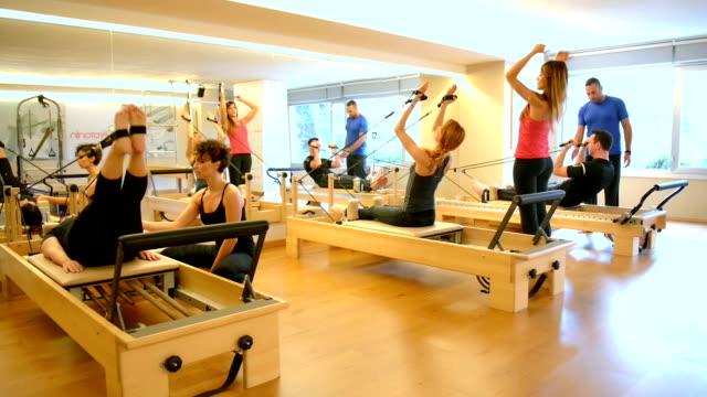 dolly: gruppo di persone con macchine esercizio di pilates - metodo pilates video stock e b–roll