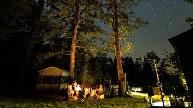 gruppe von menschen hängen an einem lagerfeuer auf einer schönen sommernacht - ferienlager stock-videos und b-roll-filmmaterial