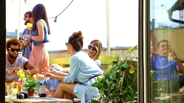vidéos et rushes de groupe de personnes à traîner à partie sur le toit - man drinking terrace