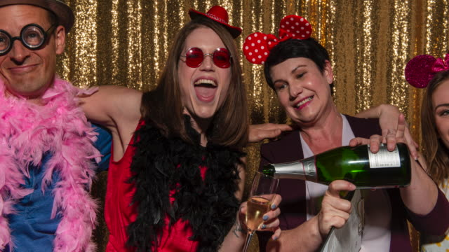 A group of people having fun wearing party props while posing in the photo booth