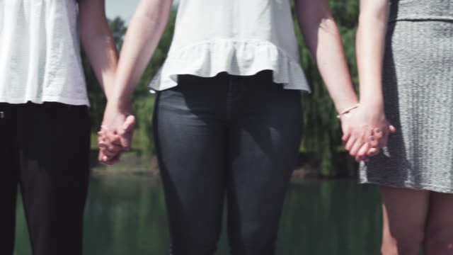 group of people holding hands outdoors (close-up) - fedeltà video stock e b–roll