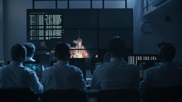 gruppe von menschen in mission control center gefüllt mit displays, feiert erfolgreichen raketenstart. elemente dieses bildes, eingerichtet von der nasa - rakete stock-videos und b-roll-filmmaterial