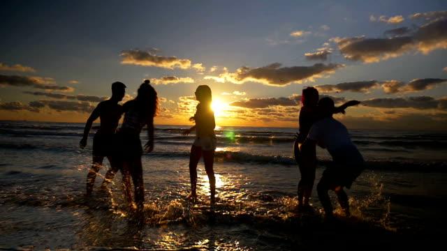 Grupo de gente saltando, bailando y divirtiéndose en el agua en la playa al atardecer en cámara lenta - vídeo