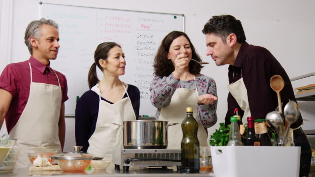 Group of people learning cooking at culinary workshop