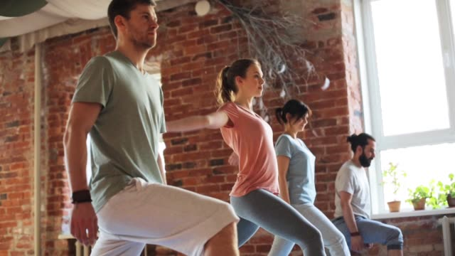 group of people making yoga exercises in gym - metodo pilates video stock e b–roll