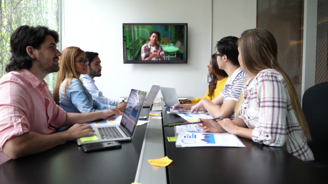 group of people on a video conference all paying attention to a black colleague talking very enthusiastic and happy - conference call stock videos & royalty-free footage