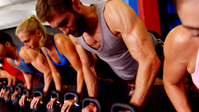 Group of people performing push-up exercise with kettlebell video