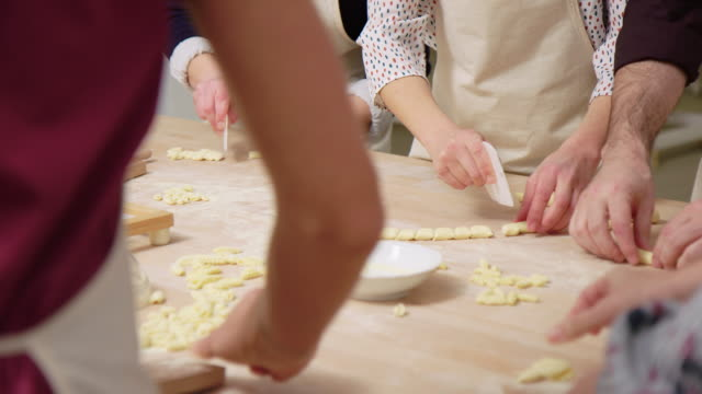Group of people preparing pasta at cooking call