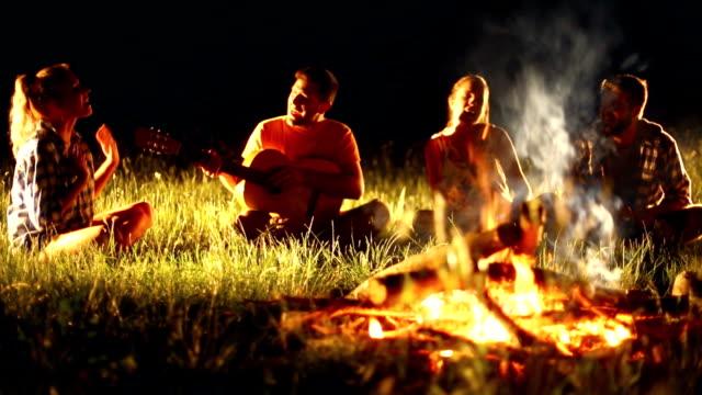 gruppe von menschen, die entspannend am lagerfeuer. - ferienlager stock-videos und b-roll-filmmaterial